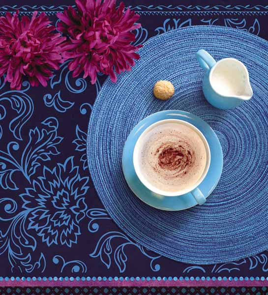 Cappuccinotasse auf einer runden, blauen Unterlage