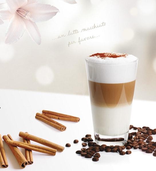 Latte Maccchiato in einem Glas , Kaffeebohnen, Zimtstangen,