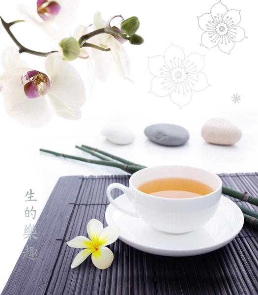 Eine weiße Teetasse auf einer schwarzen Bambusmatte, weiße Orchidee